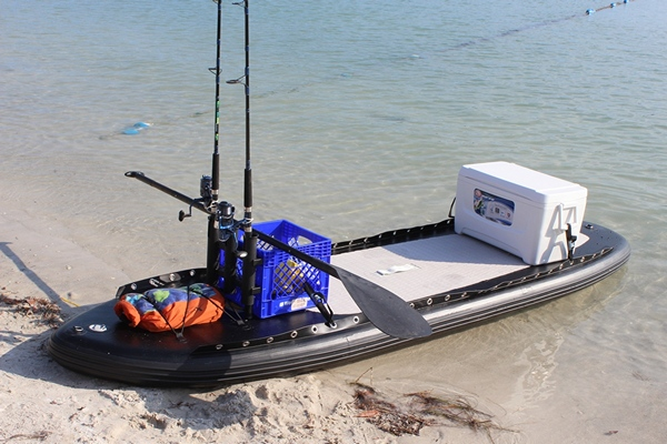 Inflatable SUP set up for fishing with fishing rod, cooler, etc.